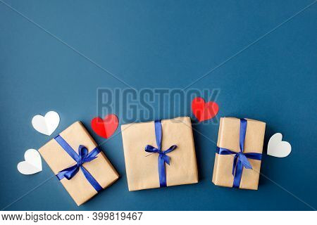 Paper Craft Gift Boxes With Bow On Blue Background With Hearts, Copy Space. Greeting Card Concept. S