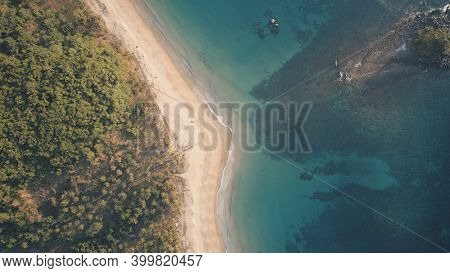 Top down of paradise resort at ocean bay aerial. Nobody tropic nature seascape at sand beach. Green tropical forest at El Nido Island, Philippines, Asia. Cinematic drone shot