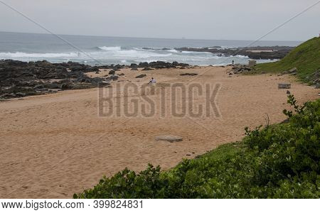 Waves Washine Onto Rocks With Beach And Natural Vegetation