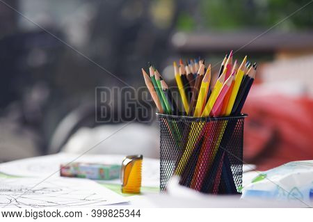 Various Colored Pencils In Black Metal Container Isolated On Gray Background. Close-up, Colorful Pen