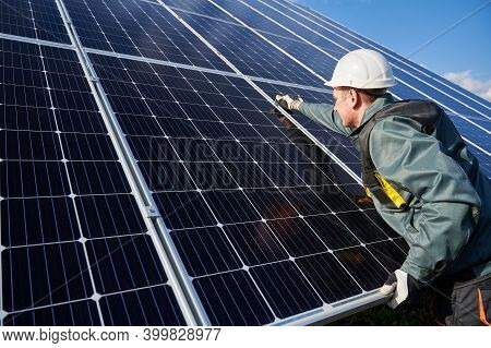 Man Technician In Safety Helmet Repairing Photovoltaic Solar Module. Electrician In Gloves Maintaini