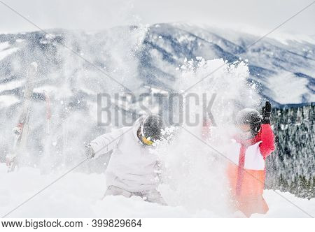 Young Couple Of Tourists Playing In Snow Against Mesmerizing Landscapes On Background, Throwing Snow