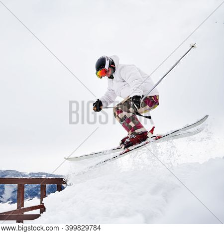 Young Man Skier In White Winter Jacket Sliding Down Snow-covered Slope On Skis. Man Freerider In Ski