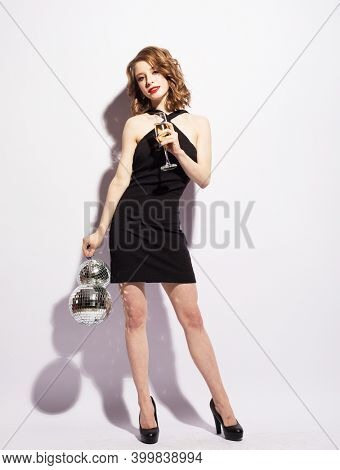 Young woman in evening dress holding champagne and disco ball. Brighrt make up and Wavy hairstyle.