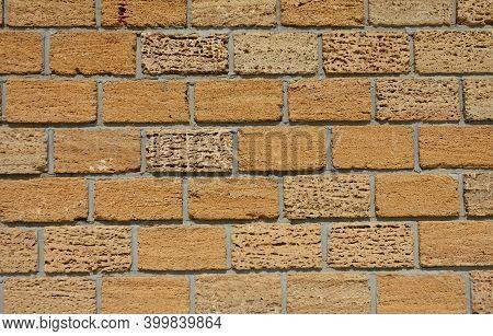 A Close-up Of An Old Yellow Limestone, Shell Rock Brick Wall Or Fence. Coquina Rock, Limestone Brick