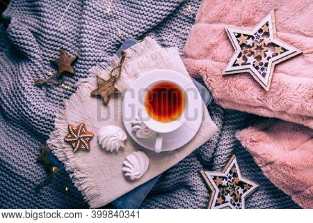 Cozy home and hygge concept with cup of tea and Christmas cookies,  warm blanket.