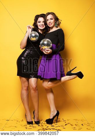Two beautiful women ready for party and drinking champagne. Best friends wearing dress and holding disco balls.