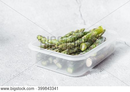 Frozen Green Asparagus Pods In A Clear White Container. On Texture. Light Background. Copyspace