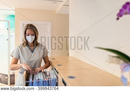 Physiotherapist Looks For File In Filing Cabinet