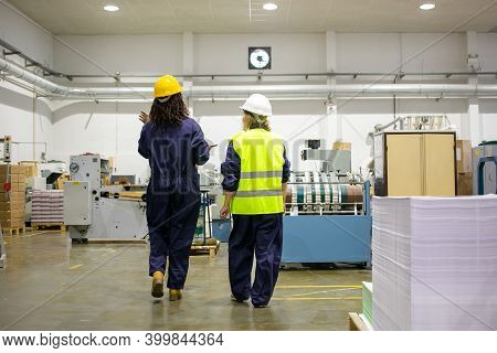 Back View Of Female Factory Workers Walking And Talking About Work. Content Experienced Women Workin