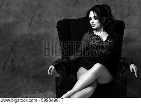 Black And White Portrait Of Gorgeous Brunette Woman In Black Lace Underwear Bodysuit Sitting In Luxu