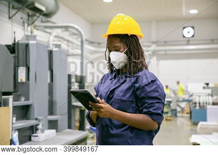 African American Female Factory Worker In Mask Holding Tablet. Focused Content Skilled Woman Working