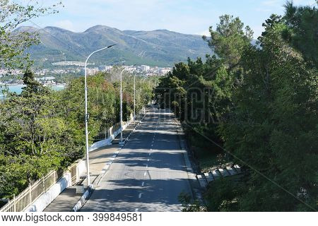 Aerial View Of A Summer Road Along The Sea And Mountains. Empty Highway With Trees And Shadows. Trav