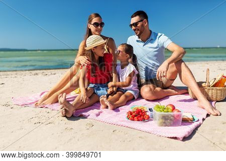 family, leisure and people concept - happy mother, father and two daughters having picnic on summer beach