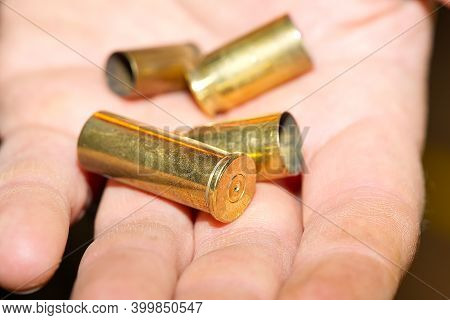 Close-up Of Bronze Cartridge Cases On A Hand In A Shooting Range Or At A Crime Scene. Crime Concept