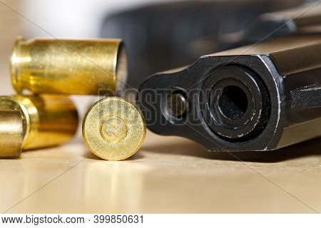 Shell Casings And Barrel Of A Pistol Close-up On A Wooden Table In A Shooting Range Or At A Crime Sc