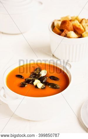 Vegetarian Autumn Pumpkin Cream Soup Served In White Cocotte With Croutons And Pumpkin Seeds On Whit