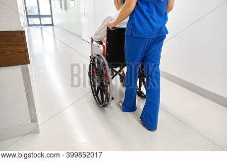 medicine, health and care concept - nurse taking senior woman patient in wheelchair at hospital corridor or nursing home