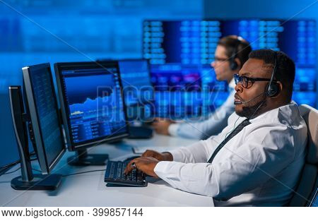Team of brokers is working in office using workstation and analysis technology. Workplace of professional traders. Global financial markets, business, currency exchange and banking concepts.