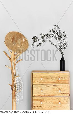 Minimalistic Hallway Interior With Trendy Wooden Clothes Hanger Stand And Commode Against A Gray Wal