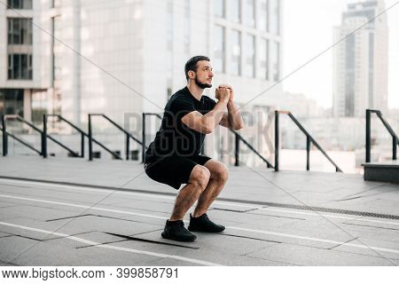 Fit Man Training Air Squat Exercise. Fit Male Exercising  Outside. Young Handsome Caucasian