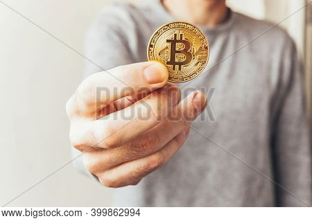 Man Hand Holding Cryptocurrency Golden Bitcoin Coin. Electronic Virtual Money For Web Banking And In