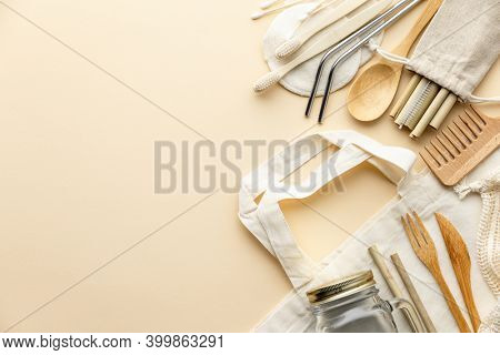 Cotton bag, bamboo cultery, glass jar, bamboo toothbrushes, hairbrush and straws on color background, flat lay.
