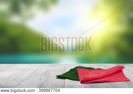 Empty Table Product. Closeup Of A Empty Red And Green Tablecloth Or Napkin On A Bright Table Over Ab
