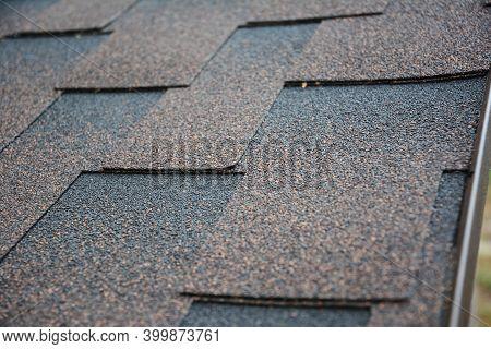 A Close-up On Architectural Asphalt Shingles Installed On A Roof.  Brown Dimensional Asphalt Shingle