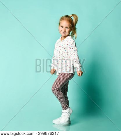Little Blonde Kid In Shirt With Hearts Print, Checkered Pants And White Sneakers. She Smiling, Danci
