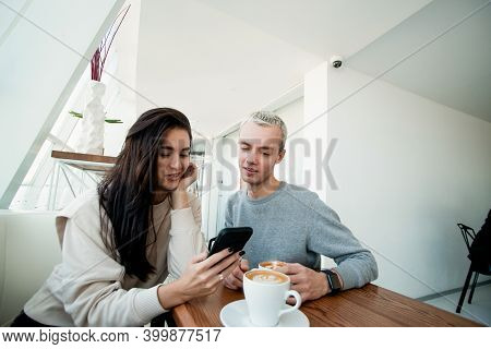 Man And Woman On Date In Cafe. Woman Shows Good Photo While Man Is Enjoying A Cup Of Cappuccino. Whi