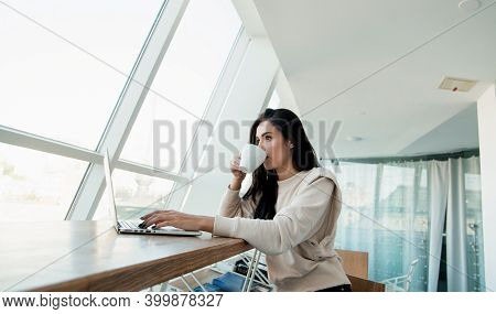 Concentrated Woman Working On Her Laptop And Drinking Coffee. Casual Clothes Concept. Brunette Woman