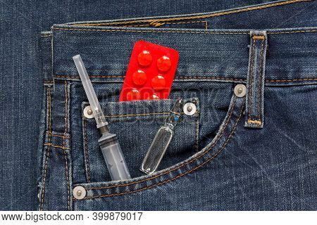 Expendable Syringe With Ampulla And Red Packaging With Pills Are Lying In Side Pocket Of Jeans. Drug