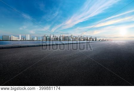 Panoramic Skyline Landscape Over The Sea And Buildings With Empty Space Dark Paved Street. Blue Sky