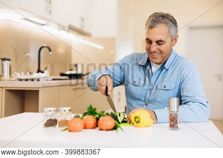 Cheerful Old Man Cuts Vegetables With A Knife In A Kitchen With White Furniture. Eat More Veggies Bl
