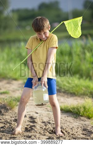 Little Boy With A Fishing Net And A Jar Of Fish.