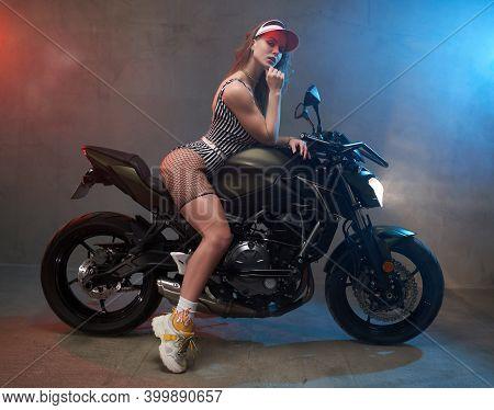 Atmospheric Smokey Studio With Custom Black Motorbike And Slim And Sexy Female Model With Cap Posing