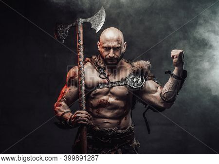Wielding An Axe And Dressed In Light Armour With Fur Bald And Furious Viking Warrior Poses In Dark A