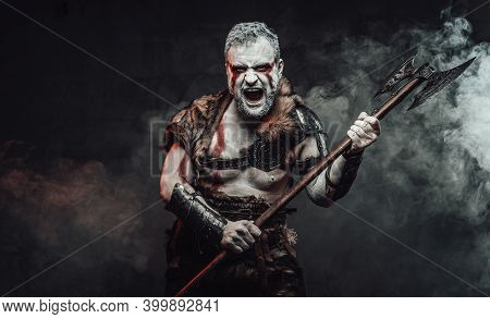 Savage And Powerful Antique Barbarian In Light Armour With Fur And Holding Two Handed Axe In Dark Fo