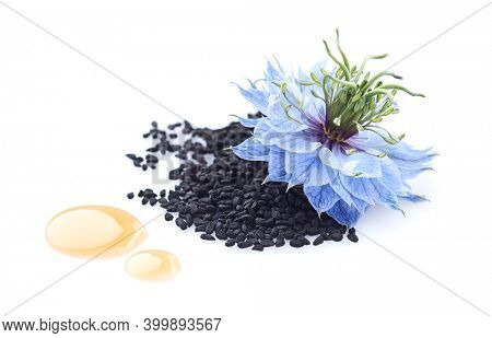 Black cumin seeds and drop oil with nigella sativa flower on white background