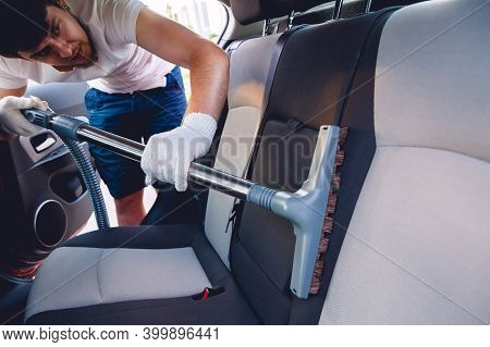 A Man Cleaning The Interior Of The Car
