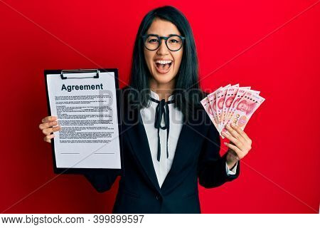 Beautiful asian young business woman holding agreement document and 100 yuan banknotes smiling and laughing hard out loud because funny crazy joke.