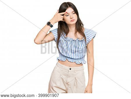Young beautiful caucasian girl wearing casual clothes pointing unhappy to pimple on forehead, ugly infection of blackhead. acne and skin problem