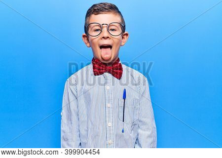 Cute blond kid wearing nerd bow tie and glasses sticking tongue out happy with funny expression. emotion concept.