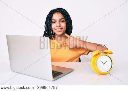 Young african american girl child with braids studying for school using laptop pointing finger to one self smiling happy and proud
