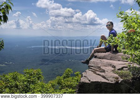 A Chinese Woman Sitting On The Edge Of A Cliff On Top Of Overlook Mountain In The Catskills In Woods
