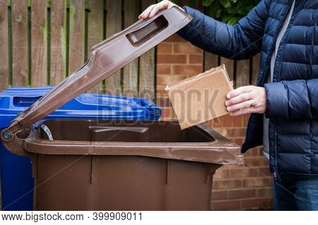 A Responsible Man Placing A Brown Cardboard Box Into A Kerbside Recycling Bin Ready For Collection A