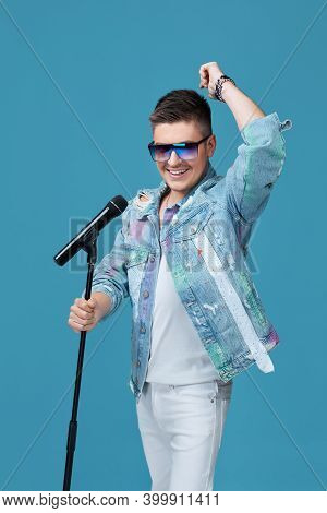 Handsome Vocalist Man In Denim And Sunglasses Singing To Microphone On Blue Background.
