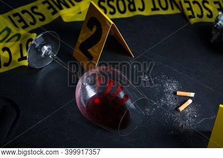 Wine Glass With Fingerprints And Stubs On Black Slate Table. Crime Scene