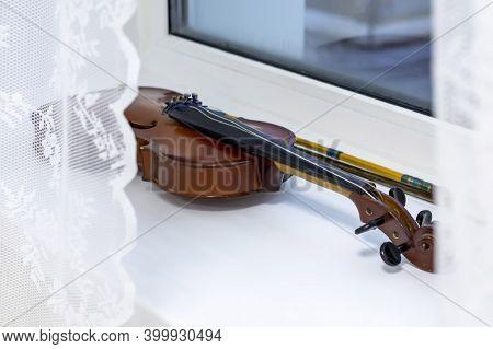 A Broken Violin Lies On A White Windowsill.